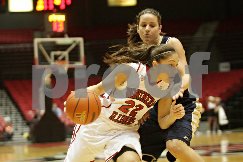 Rob Winner – rwinner@shawmedia.com<br /> <br /> Northern Illinois point guard Amanda Corral (22) drives to the basket past Akron's Hanna Luburgh during the first half in DeKalb, Ill., Wednesday, Jan. 16, 2013.