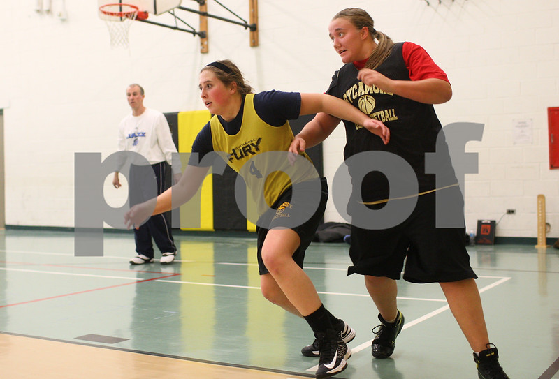 Kyle Bursaw – kbursaw@shawmedia.com<br /> <br /> Sycamore sophomore Bailey Gilbert (front) and junior Beth Slavens battle <br /> to rebound a ball shot by coach Brett Goff (background) at practice on Wednesday, Jan. 16, 2013.