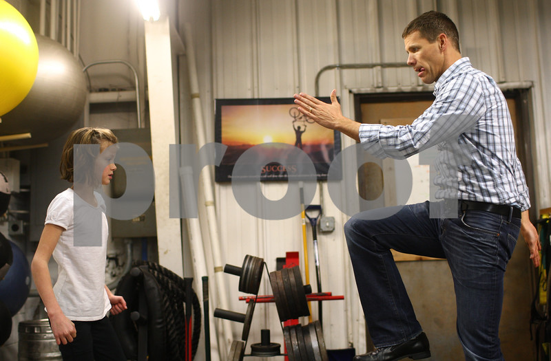 Kyle Bursaw – kbursaw@shawmedia.com<br /> <br /> Frank Heegaard demonstrates a stability exercise for his 9-year-old daughter Janae to do at Moose (L)-Up in Sycamore, Ill. on Friday, Jan. 11, 2013. Doctors found a Wilms' tumor in Janae's kidney when she was five years old. As a result of the chemotherapy, one of Janae's kidneys was removed and she also developed neuropathy, which led to some stunted growth in her legs and Achilles tendon. Her parents were told that Janae would recover about 90 to 95% but would probably not be able to play on a competitive level in sports that required heavy use of the legs.