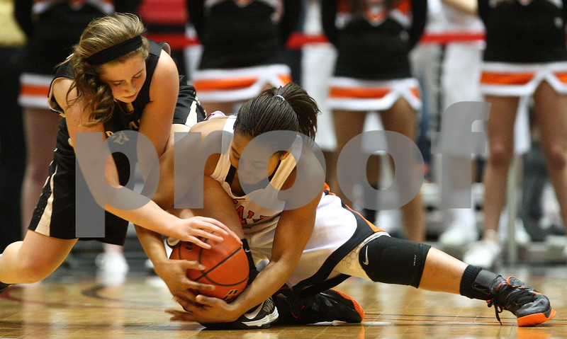 Kyle Bursaw — kbursaw@shawmedia.com<br /> <br /> Sycamore's Bailey Gilbert and DeKalb's Courtney Patrick both vie for the ball in the second quarter of the game. DeKalb defeated Sycamore 36-18 in their annual game at the Convocation Center in DeKalb, Ill. on Friday, Jan. 25, 2013.