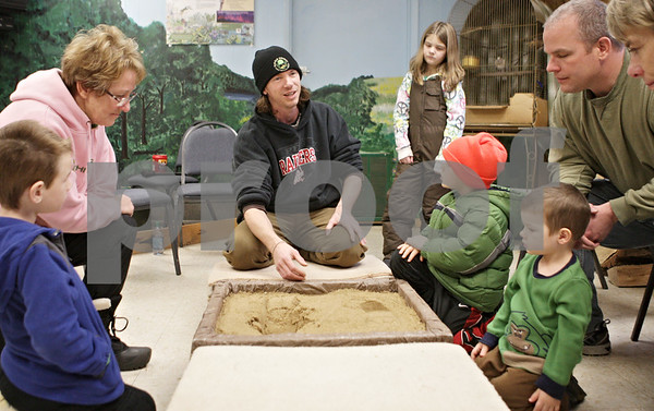 Rob Winner – rwinner@shawmedia.com<br /> <br /> Jason Thompson (center) uses a box of sand and his footprints to teach a group all about tracking during WinterFest at the Russell Woods Forest Preserve in Genoa, Ill., Saturday, Jan. 19, 2013.