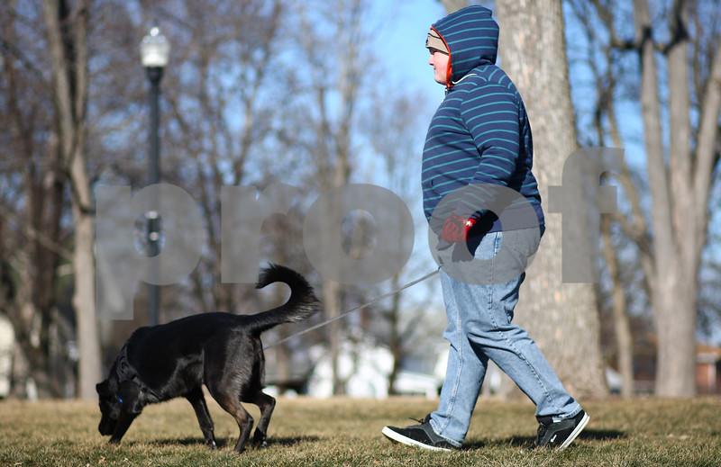 Kyle Bursaw – kbursaw@shawmedia.com<br /> <br /> DeKalb resident Matt Callahan, 14, walks his two-year-old golden retriever/German shepherd mix Buddy through Huntley Park on Monday, Jan. 21, 2013.