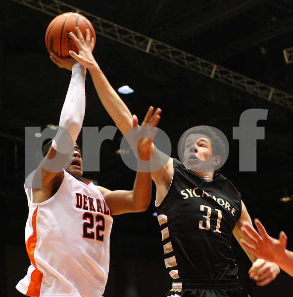 Kyle Bursaw — kbursaw@shawmedia.com<br /> <br /> Sycamore's Logan Wright tries to block DeKalb's Andre Harris but is called for a foul in the second quarter. DeKalb and Sycamore faced off in their annual game at the Convocation Center in DeKalb, Ill. on Friday, Jan. 25, 2013.