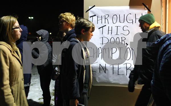 Kyle Bursaw – kbursaw@shawmedia.com<br /> <br /> DeKalb High School marching band players, parents and staff walk past a door with one of the many signs made welcoming them back to DeKalb on Thursday, Jan. 3, 2013 from their trip to play at the Sugar Bowl. The sign reads 'Through this door, champions enter,' referring to the marching band's first place overall performance in the competition on December 31.