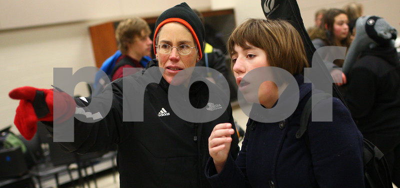 Kyle Bursaw – kbursaw@shawmedia.com<br /> <br /> Sophia Varcados (left) tries to find her daughter, Zoe Markle (right), in an overhead picture of the marching band competing in New Orleans hanging in the band room on Thursday, Jan. 3, 2013. Varcados and many other parents welcomed the band back from the first place victory in the competition and Sugar Bowl performance with signs, balloons, luminarias and other decorations.