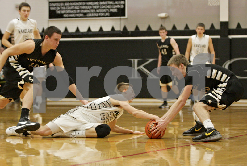 Rob Winner – rwinner@shawmedia.com<br /> <br /> Kaneland's Dan Miller (22) and Sycamore's Ben Niemann struggle for possession of a ball during the third quarter in Maple Park, Ill., Tuesday, Jan. 22, 2013. Kaneland defeated Sycamore, 43-42.