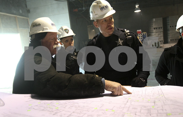Kyle Bursaw – kbursaw@shawmedia.com<br /> <br /> Emery Harmon (left), the superintendent for the DeKalb police station project with Irving Construction, point out a portion of the plan to DeKalb officers Sadie Pristave (back center) and Todd Wells (right) on Monday, Jan. 14, 2013. The station is on track to open in late 2013.