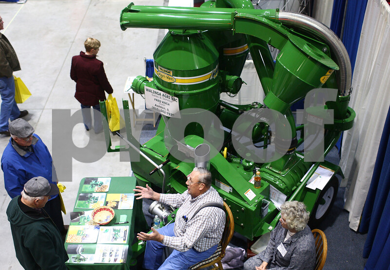 Kyle Bursaw – kbursaw@shawmedia.com<br /> <br /> Frederick and Anita Koch (bottom center and right) discuss Walinga's Agri-Vac products with visitors to their booth at the Northern Illinois Farm Show at the Convocation Center on Thursday, Jan. 10, 2013.