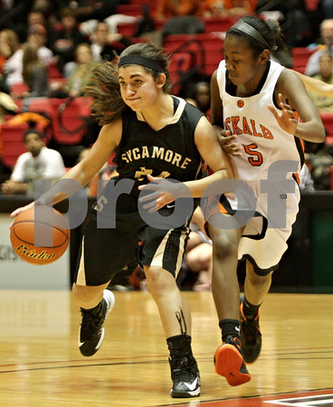 Rob Winner – rwinner@shawmedia.com<br /> <br /> Sycamore's Julia Moll (left) moves the ball while being pressured by DeKalb's Jasmine Malloy during the first quarter at the Convocation Center in DeKalb, Ill., Friday, Jan. 25, 2013.