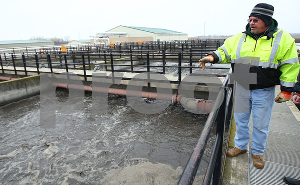Kyle Bursaw – kbursaw@shawmedia.com<br /> <br /> Fred Busse, director of Sycamore Public Works, points to some of the wastewater treatment plant's digesters and aerator tanks in Sycamore, Ill. on Wednesday, Jan. 23, 2013. The existing tanks are about 35 years old and additional tanks are coming in the renovations for the plant.