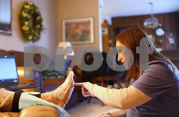 Kyle Bursaw – kbursaw@shawmedia.com<br /> <br /> Amie Eads, a registered nurse with KishHealth's homecare program, inspects patient Bob Jackson's foot to monitor the healing process of a diabetic ulcer on his foot in Jackson's DeKalb home on Thursday, Jan. 17, 2013.
