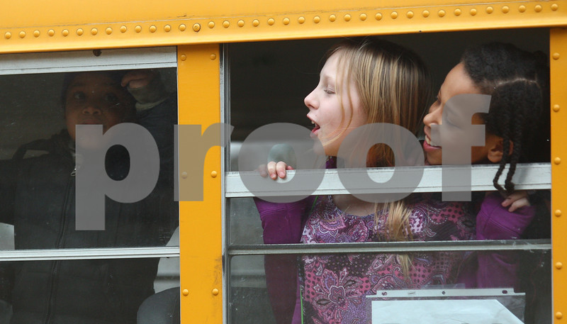 Kyle Bursaw – kbursaw@shawmedia.com<br /> <br /> Kasey Nelson (center) and Kameron Hill (right), both 10, call out to a friend from their school bus window after school at Founders Elementary on Thursday, Jan. 10, 2013.