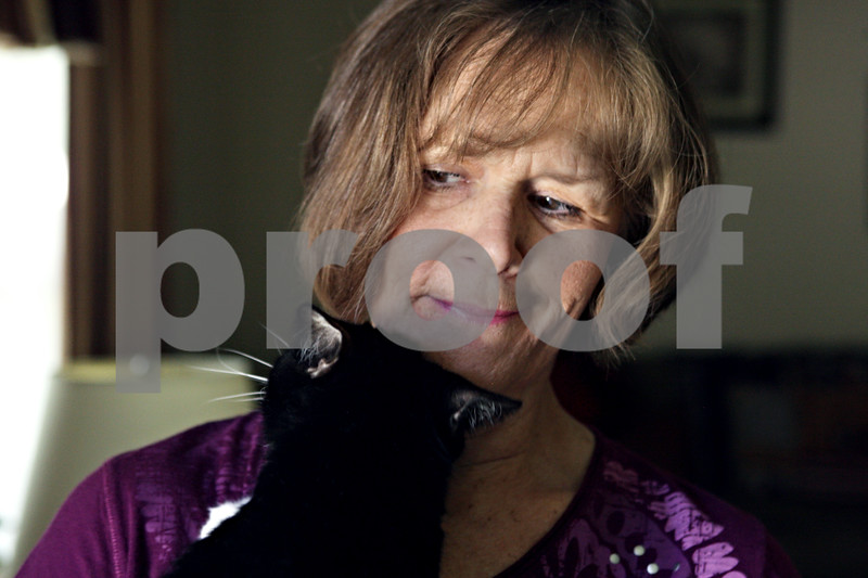 Rob Winner – rwinner@shawmedia.com<br /> <br /> Linda Chapman is snuggled by her cat at her DeKalb home on Friday, June 28, 2013. Chapman, who taught at Central High School in Burlington, is eagerly watching the state to see how it enacts pension reform.