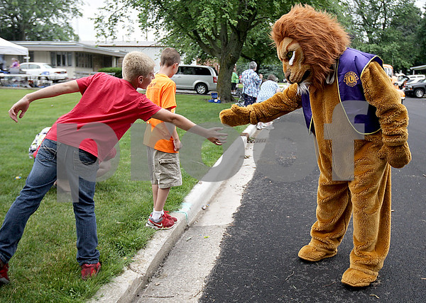 Monica Maschak - mmaschak@shawmedia.com<br /> A lion, with the Shabbona Lions Club, high fives a specatator at the annual Shabbona Parade on Saturday, June 29, 2013.