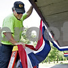 Monica Maschak - mmaschak@shawmedia.com<br /> Randy Hjelmberg, with the DeKalb Park District grounds and maintenance, takes down the patriotic bunting from the Dee Palmer Band Shell the morning after a few thousand people gathered to watch Fourth of July fireworks at Hopkins Park.