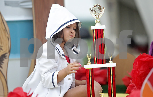 Monica Maschak - mmaschak@shawmedia.com<br /> Sadie Jimenez, 6, admires the trophy for first place float in the Shabbona Parade on Saturday, June 29, 2013. Jimenez rode on a Wizard-of-Oz-themed float for the United Church of Christ.
