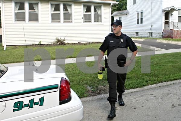 Rob Winner – rwinner@shawmedia.com<br /> <br /> Officer Jared Burke heads to his vehicle parked in front of his home before the start of his shift in DeKalb, Ill. on Thursday, June 27, 2013. Burke, who lives on North Eleventh Street with his family, is taking part in DeKalb's resident officer program.
