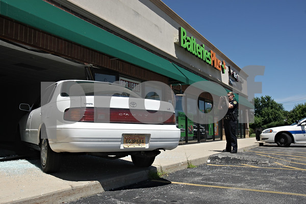 Rob Winner – rwinner@shawmedia.com<br /> <br /> A Sycamore police officer takes a photograph of a car that jumped a curb and went into a vacant storefront at 1565 DeKalb Avenue in Sycamore on Friday afternoon.