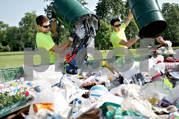 Monica Maschak - mmaschak@shawmedia.com<br /> Cory Lesniak and Casey Smith, with the DeKalb Park District, dump out full trash cans into a disposal unit the morning after a few thousand people gathered to watch Fourth of July fireworks at Hopkins Park.