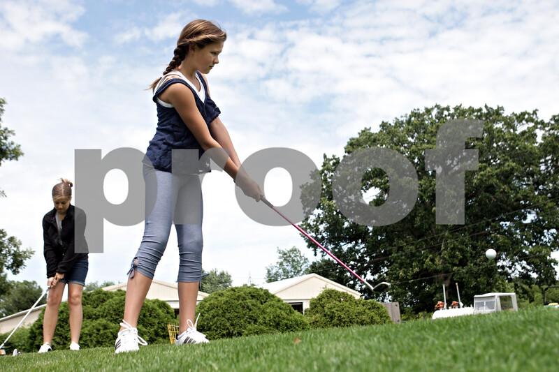 Rob Winner – rwinner@shawmedia.com<br /> <br /> Gwyn Golembiewski (front), 11, and Sydney McNett, 11, work on their chipping skills at the Buena Vista Golf Course in DeKalb, Ill., Tuesday, July 2, 2013.