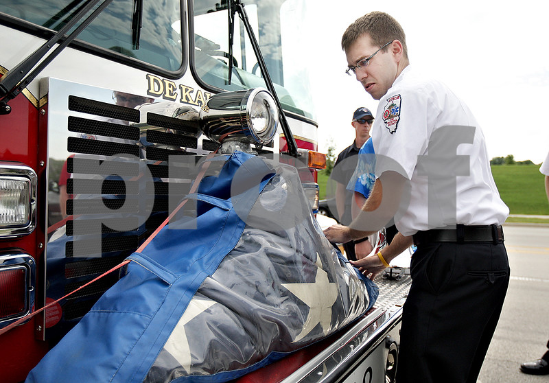 Monica Maschak - mmaschak@shawmedia.com<br /> Utica Assistant Fire Chief Ben Brown ties the National 9/11 Flag to the front of a DeKalb fire engine for the procession to DeKalb High School on Satuday, July 6, 2013. The Warriors' Watch Riders escorted the flag to the school, where it was part of the opening ceremony for the Illinois Chaos Football game.