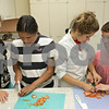 Rob Winner – rwinner@shawmedia.com<br /> <br /> (From left to right) Megan Moran, 18, helps Stephannie Baccay, 16, while McKenzie Palm, 17, helps Cody Marbutt, 17, slice up a tomato during a cooking for the visually impaired class at Sycamore High School on Thursday, July 11, 2013.