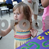 Monica Maschak - mmaschak@shawmedia.com<br /> Isabelle Rolli, 3, of DeKalb, looks at her hand after finger painting flowers onto a sign for the DeKalb County Gardens Project during a Tuesdays on the Town: Salute to America event in Sycamore on July 9, 2013. Tuesdays on the Town are presented by the city of Sycamore and Discover Sycamore.