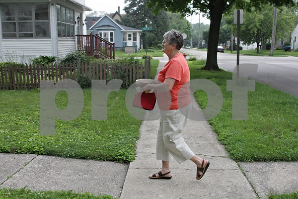 Rob Winner – rwinner@shawmedia.com<br /> <br /> Volunteer Dee Anderson carries a meal to a Meals on Wheels client in DeKalb, Ill., Tuesday, July 9, 2013.