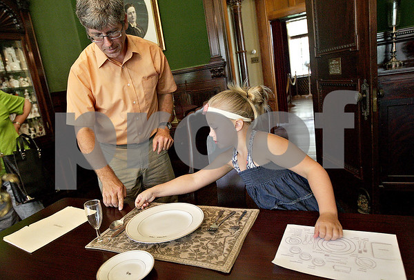 Monica Maschak - mmaschak@shawmedia.com<br /> Piper Schiola-Williams, 6, sets the Ellwood's dining room table with the help of docent Damon Geiger during a staff and servants tour of the Ellwood House in DeKalb on Wednesday, July 10, 2013. Tourists watched a short film on the staff and servants of the house, then picked a member to role play during the tour of the house.