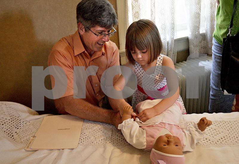Monica Maschak - mmaschak@shawmedia.com<br /> Amanda Gorlewski, 4, pins a cloth diaper on to a baby doll with the help of docent Damon Geiger during a staff and servants tour of the Ellwood House in DeKalb on Wednesday, July 10, 2013. Tourists watched a short film on the staff and servants of the house, then picked a member to role play during the tour of the house.