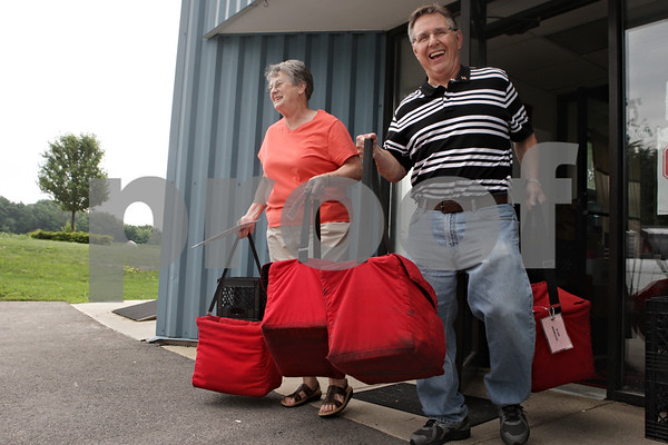 Rob Winner – rwinner@shawmedia.comOn Tuesday at the Voluntary Action Center in Sycamore, volunteer Dee Anderson (left) is helped by coordinator Ron Mullen while carrying prepared meals to Anderson's vehicle to be delivered to Meals on Wheels clients.