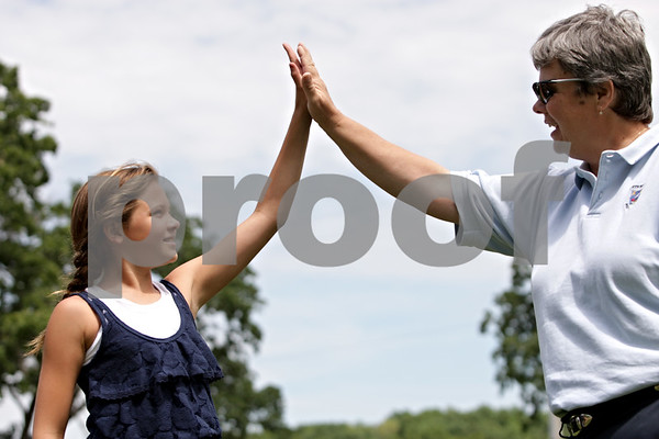Rob Winner – rwinner@shawmedia.com<br /> <br /> Gwyn Golembiewski (left), 11, high-fives Pam Tyska at the Buena Vista Golf Course in DeKalb, Ill., Tuesday, July 2, 2013.