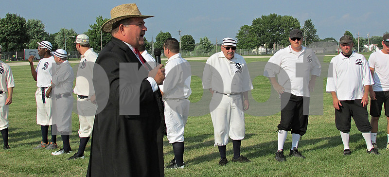 """Baseball arbitrator Tom """"Bull"""" Abens addresses the crowd as members of the Somonauk Blue Stockings and the Sandwich Millers look on. The Blue Stockings players wore white uniforms with dark socks, while the Millers players wore black pants and hats with their white shirts. The prize of the game: $10 and a trophy bat."""