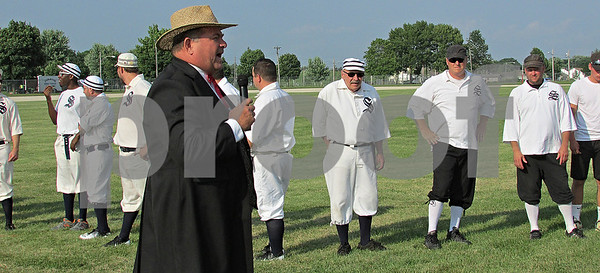 "Baseball arbitrator Tom ""Bull"" Abens addresses the crowd as members of the Somonauk Blue Stockings and the Sandwich Millers look on. The Blue Stockings players wore white uniforms with dark socks, while the Millers players wore black pants and hats with their white shirts. The prize of the game: $10 and a trophy bat."