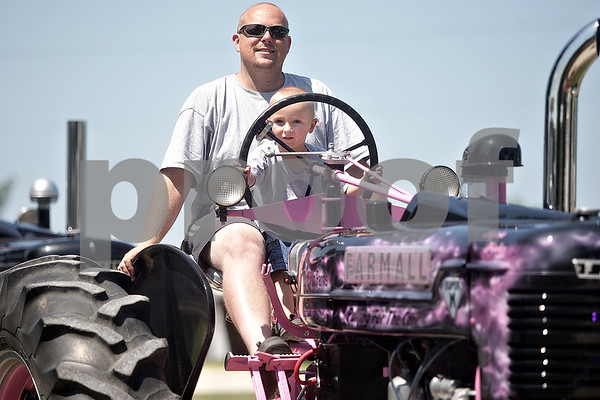Monica Maschak - mmaschak@shawmedia.com<br /> Randy Wilkening and son Kayden Wilkening, of Hinckley, ride their pink 1953 Farmall Super M in the tractor and truck Parade of Power at the Waterman Lions Club 13th Annual Summer Fest at Waterman Lions Park on Saturday, July 20, 2013. The tractor is in honor of Dolores Wilkening and Laurie Whitt for breast cancer awareness.