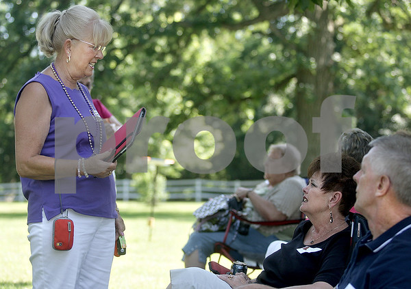 Monica Maschak - mmaschak@shawmedia.com<br /> Marilyn Challand, class of 1966, chats with Jackie Wallin, class of 1965, about her iPad at a Baby Boomer Bash for Sycamore High School graduates from the 1960s held at the Criswell residence in Genoa on Saturday, July 13, 2013. The baby boomers have a reunion every two years.