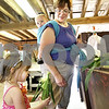 Monica Maschak - mmaschak@shawmedia.com<br /> Christi Bedell hands her daughter, Celia Bedell, 3, an ear of corn as they shop for fresh produce on the first day of sweet corn sales at Wiltse Farm in Maple Park on Wednesday, July 17, 2013. The sweet corn will be freshly picked daily.