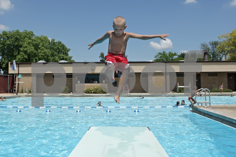 Rob Winner – rwinner@shawmedia.com<br /> <br /> Timothy Overton, 7, of Sycamore, jumps backward off of a diving board at the Sycamore Park District Pool on Monday, July 15, 2013.