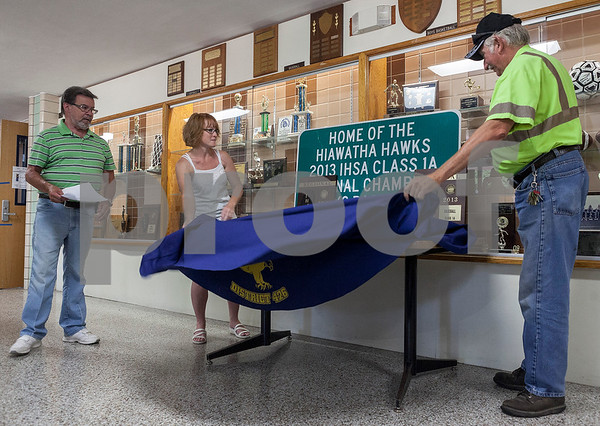Erik Anderson - For the Daily Chronicle<br /> Less Bellah, Mayor of Kirkland, (from left) watches as Sarah Ziegler and Harry Newberry pull off the sheath showcasing the new regional championship road sign at Hiawatha High School in Kirkland on Wednesday, July 17, 2013. The Hawks Baseball and Softball teams made school history by both winning the IHSA Regional Championship in 2013.
