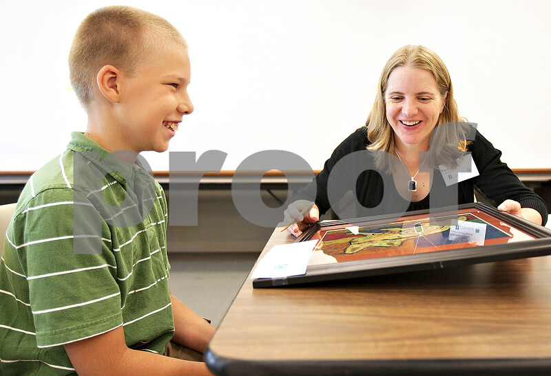 Monica Maschak - mmaschak@shawmedia.com<br /> Jared Clausen, 10, discusses his abstract art piece with judge Rachel Xidis during the 4-H judging day at the DeKalb County Farm Bureau Wednesday, July 17, 2013. 4-H, an organization by the University of Illinois Extension, is for children ages 8 to 18, that stands for head, heart, health and hands. Children explore different paths of creativity, make projects and have them judged.