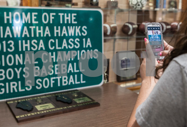 Erik Anderson - For the Daily Chronicle<br /> Recent graduate of Hiawatha High School, Abigail Turner, takes a photo of the new road sign on her cellphone after the initial unveiling at Hiawatha High School in Kirkland on Wednesday, July 17, 2013. The Hawks Baseball and Softball teams made school history by both winning the IHSA Regional Championship in 2013.
