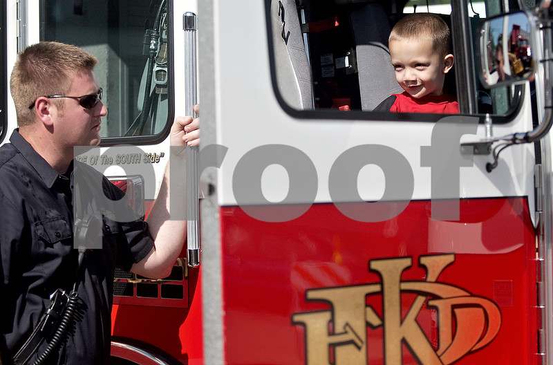 Monica Maschak - mmaschak@shawmedia.com<br /> Firefighter Paramedic Jarrett Throp talks to Damien Cavazos, 3, who is seated in the fire truck, at the Fourth Street Family Fun Fest in front of the DeKalb Education Center on Tuesday, July 23, 2013.