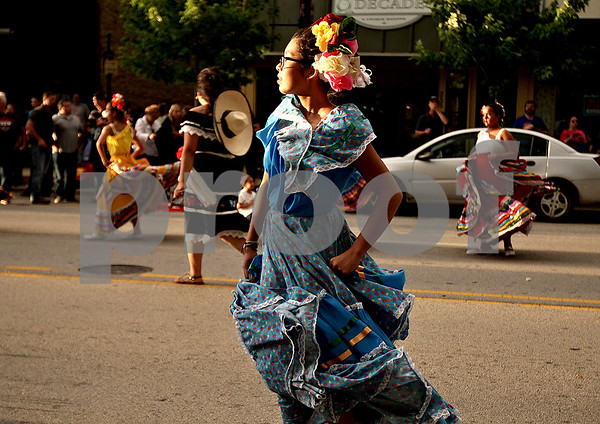 Monica Maschak - mmaschak@shawmedia.com<br /> Celia Huerta, 13, with the Rietos del Sol, dances in the street with her peers as part of the Kishwaukee Fest Parade in Downtown DeKalb on Friday, July 26, 2013.