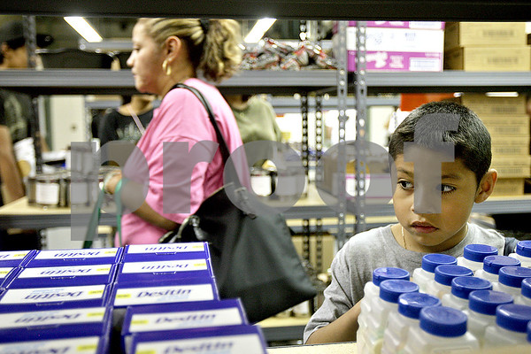 Monica Maschak - mmaschak@shawmedia.com<br /> Joshua D'los Santos, 6, looks at items on a shelf while shopping with his mother, Rocio Delgado (right), at the Barb Food Mart at Huntley Middle School on Thursday, July 25, 2013. The food mart is put on by the Northern Illinois Food Bank and is held every Thursday at the middle school from 3 p.m. to 5 p.m. Clients must have a child in a District 428 school to participate.