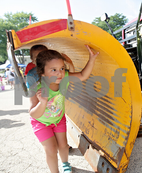 Monica Maschak - mmaschak@shawmedia.com<br /> Isabella Donegan, 3, of DeKalb, leads a line of kids under the snow plow of a DeKalb Township plow truck at the Fourth Street Family Fun Fest in front of the DeKalb Education Center on Tuesday, July 23, 2013.