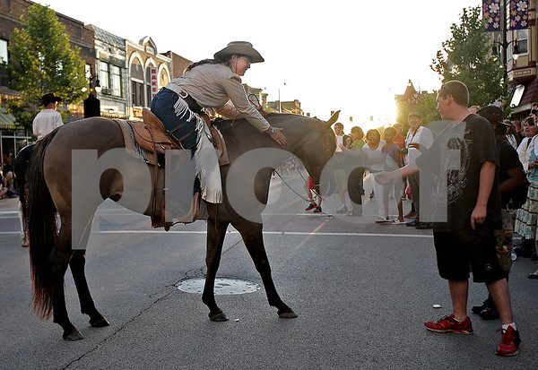 Monica Maschak - mmaschak@shawmedia.com<br /> Laura Johnson, with the Northern Illinois Outlaws, pulls up to the crowd to let parade-goers pet her horse during of the Kishwaukee Fest Parade in Downtown DeKalb on Friday, July 26, 2013.