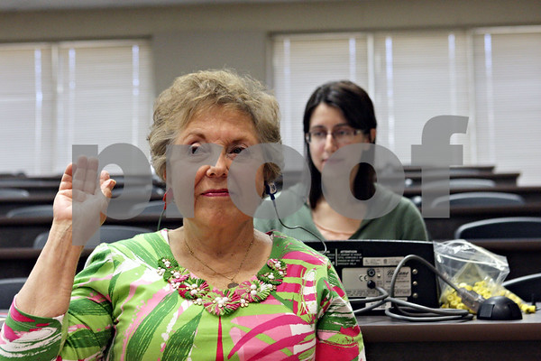 Rob Winner – rwinner@shawmedia.com<br /> <br /> Nancy Watson (left) of Sycamore raises her right hand to indicate she can hear a sound while taking a hearing test administered by Northern Illinois University audiology graduate student Emily Bates during the 2013 Senior Health Fair hosted by the Family Service Agency and the Voluntary Action Center at DeKalb High School on Thursday, July 25, 2013.