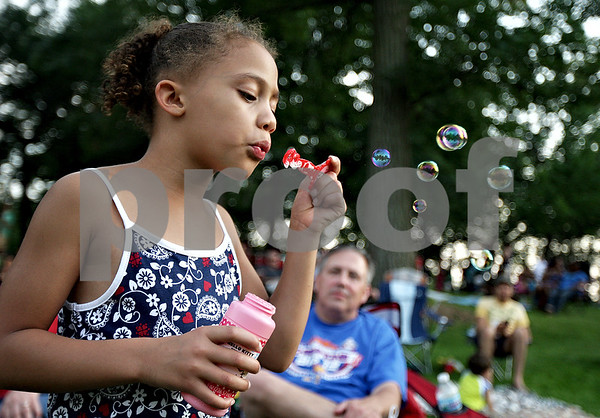Monica Maschak - mmaschak@shawmedia.com<br /> Sami Simms, 5, of Sycamore, blows bubbles while she waits for fireworks at the Fourth of July celebration at Hopkins Park in DeKalb.