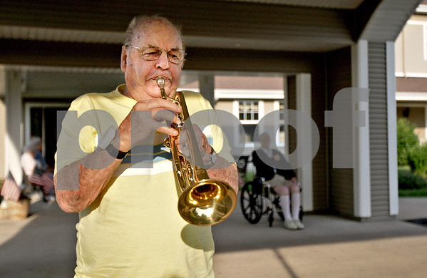 """Monica Maschak - mmaschak@shawmedia.com<br /> Sam Jones, 82, a resident at Grand Victorian in Sycamore, plays taps on his trumpet by the flag poles in front of the assisted-living home on Tuesday, July 2, 2013. Jones, a Korean War Veteran, has been playing taps every night at 6:45 p.m. since he moved to the home two years ago. """"I play for the veterans and those that died,"""" Jones said."""