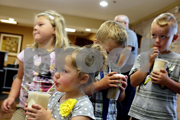 Rob Winner – rwinner@shawmedia.com<br /> <br /> (From left to right) Siblings Lilli Weber, 5, Londyn Weber, 2, Logan Weber, 4, and Landon Weber, 7, all enjoy a root beer float after visiting a resident at Pine Acres Rehabilitation and Living Center in DeKalb, Ill., Friday, June 7, 2013. Residents at Pine Acres were running the stand and selling the floats for 75 cents. All of the proceeds will benefit the Kishwaukee College Foundation.